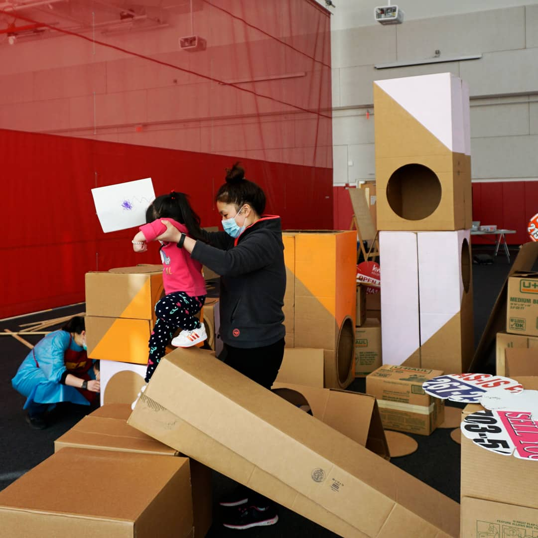 Mother helps kid climb over cardboard boxes