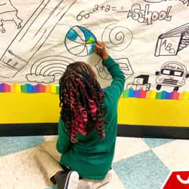 A child draws a basketball on the wall